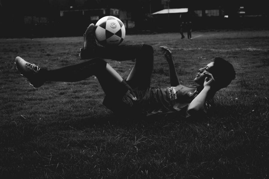 Fodboldspiller jonglerer med bolden - sort hvid foto