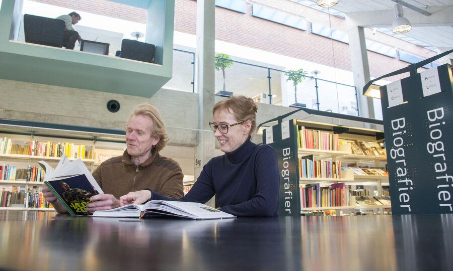 To personer læser bøger ved et bord