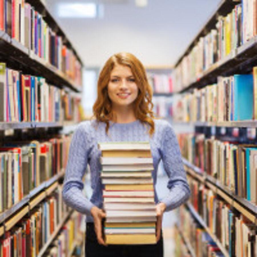 Billede af bibliotekar med stak af bøger
